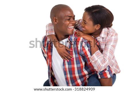 cheerful young black couple piggybacking on white background - stock photo