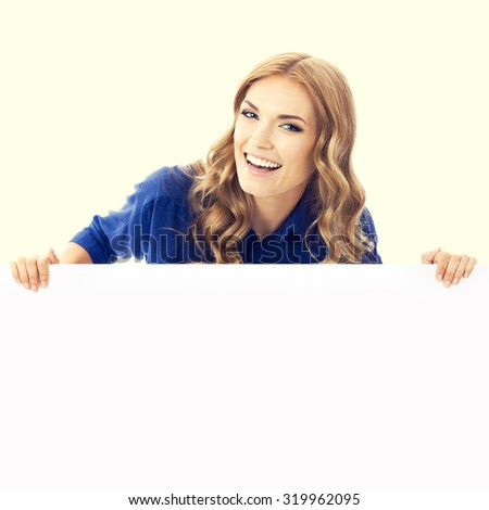 Cheerful young blond businesswoman showing blank signboard with copyspace area for slogan or text message - stock photo