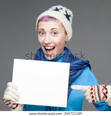 cheerful young blond caucasian woman in winter clothing holding sign over gray background - stock photo