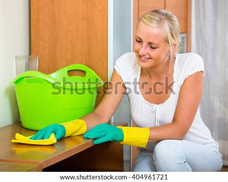 Cheerful young blonde woman in rubber gloves cleaning indoors  - stock photo