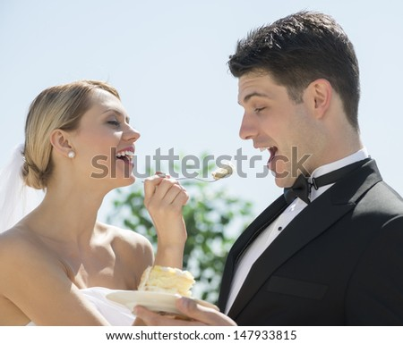 Cheerful young bride feeding wedding cake to groom outdoors - stock photo