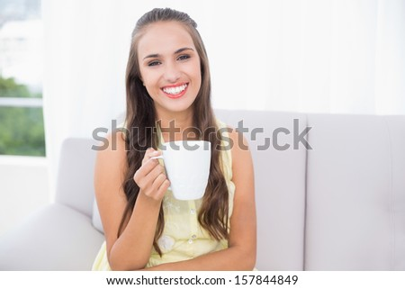 Cheerful young brunette holding a mug in bright living room