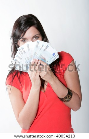 Cheerful young brunette lady holding cash and smiling - stock photo