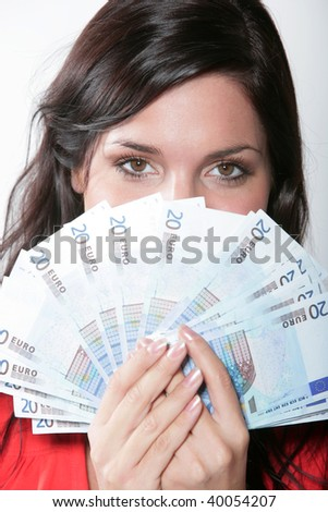 Cheerful young brunette lady holding cash and smilingt - stock photo