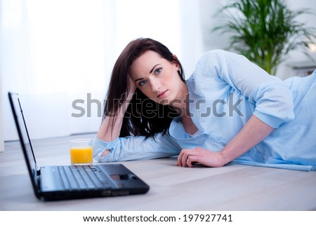 Cheerful young brunette lying on the floor at home with laptop relaxed