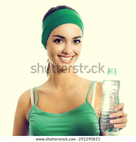 Cheerful young brunette woman in green fitness wear drinking water - stock photo