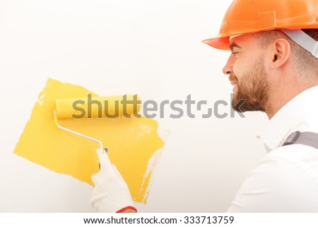 Cheerful young builder is painting wall with yellow color. He is standing and smiling. The man is holding a roller - stock photo