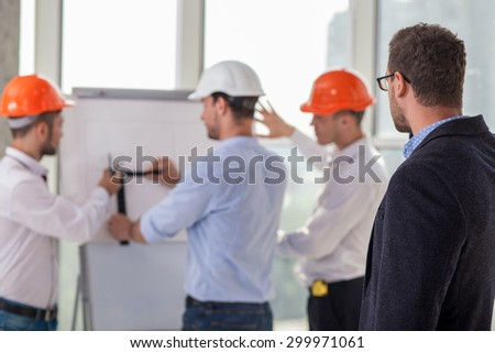 Cheerful young builders are drawing a layout of new building with aspirations. The customer is watching their job with attention. Focus on the client - stock photo