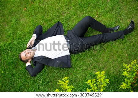 Cheerful young businessman calling by phone lying on green grass - stock photo
