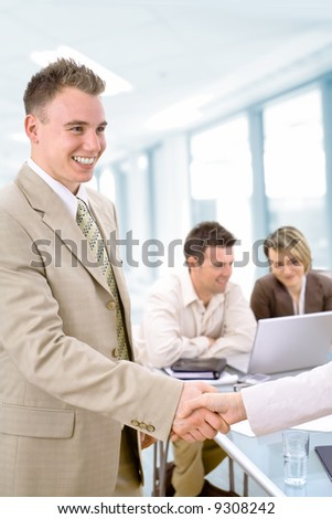 Cheerful young businessman greeting partner in office.