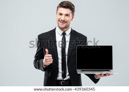 Cheerful young businessman holding blank screen laptop and showing thumbs up over white background - stock photo