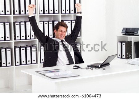 cheerful young businessman in office - stock photo