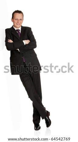 Cheerful young businessman leans against wall. Isolated on white background. - stock photo