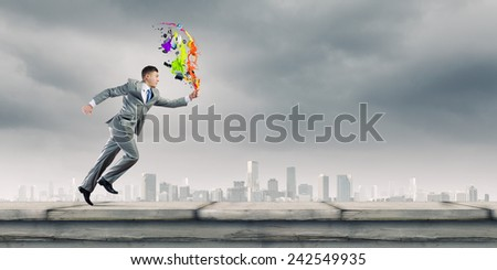 Cheerful young businessman running in a hurry - stock photo