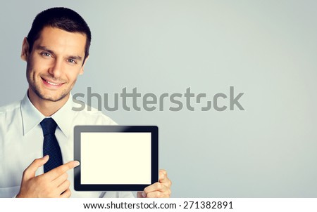 Cheerful young businessman showing blank no-name tablet pc monitor, with copyspace area for text or slogan, specially toned - stock photo