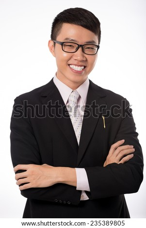 Cheerful young businessman standing with his arms crossed