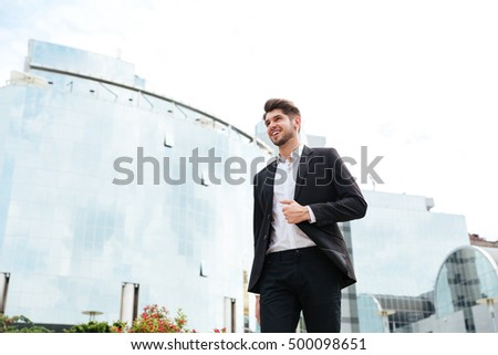 Cheerful young businessman walking outdoors near business center