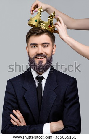 Cheerful young businessman, with violet beard and eyebrows, wearing in dark blue suit and tie, posing when girls hands holding crown over his head and smiling, on white background, in studio, waist up - stock photo