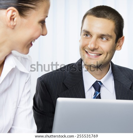 Cheerful young businesspeople working with laptop at office - stock photo