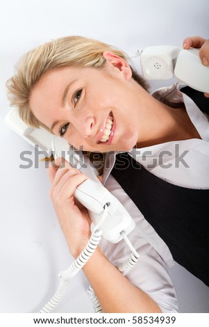 cheerful young businesswoman answering a lot of phones at same time - stock photo