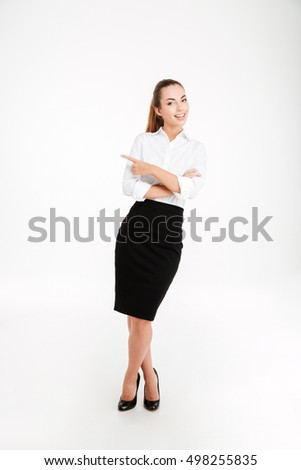 Cheerful young businesswoman pointing finger away and looking at camera over white background
