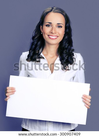 Cheerful young businesswoman showing blank signboard with copyspace area for text or slogan, posing at studio, over violet background - stock photo