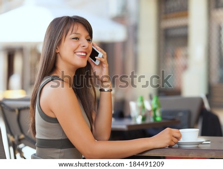 Cheerful young businesswoman talking on the phone outdoors
