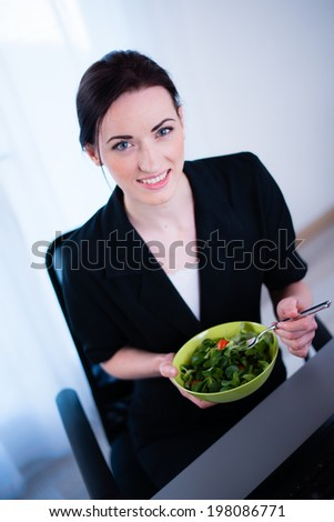 cheerful young caucasian business woman enjoying fresh salad for lunch break at office desk - stock photo