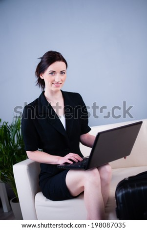 cheerful young caucasian business woman siting with laptop computer