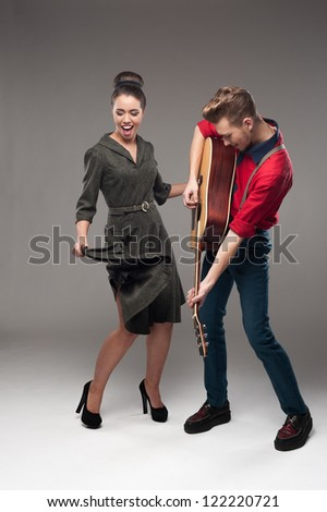 cheerful young caucasian guitar player and dancing girl in vintage clothing over gray background
