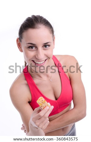 cheerful young caucasian woman eating diet cereal bar - stock photo