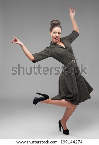 cheerful young caucasian woman in green vintage dress dancing isolated on gray