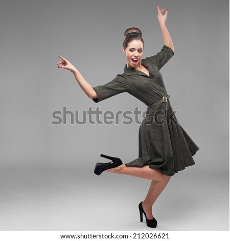 cheerful young caucasian woman in green vintage dress dancing on gray - stock photo