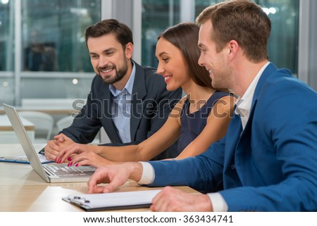 Cheerful young colleagues are discussing plan of work in conference hall. They are sitting at the desk and looking at the laptop. The woman is typing wit joy. The men are smiling - stock photo
