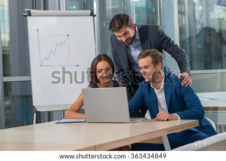 Cheerful young colleagues are using a laptop for conference. They are looking at screen in office and smiling. The businessman and woman are sitting at desk. Another man is standing near them - stock photo