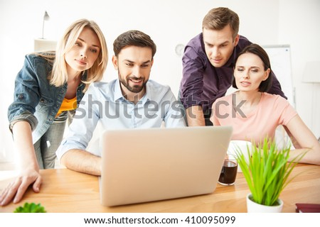 Cheerful young colleagues are using computer for work - stock photo