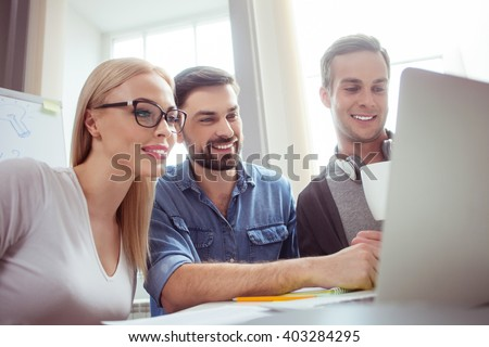 Cheerful young colleagues are working with computer - stock photo