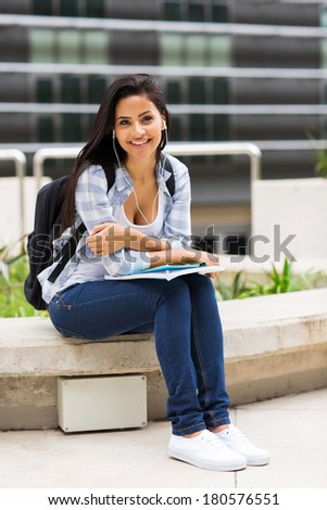 cheerful young college student sitting outside campus building - stock photo