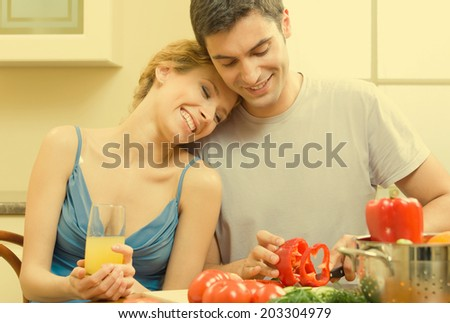Cheerful young cooking couple prepairing vegetarian salad at home