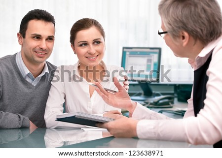 Cheerful young couple at financial planning consultation - stock photo