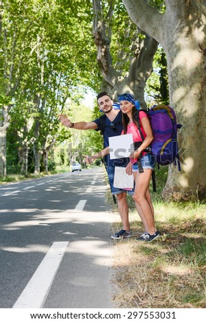 cheerful young couple backpacker hitchhiking on a roadside in summer vacation - stock photo