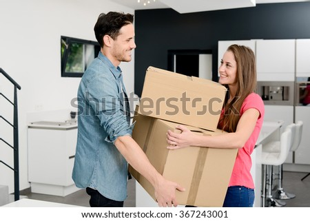 cheerful young couple carrying box and moving in new modern design house