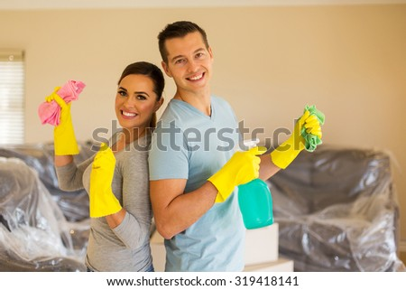 cheerful young couple cleaning their new house - stock photo