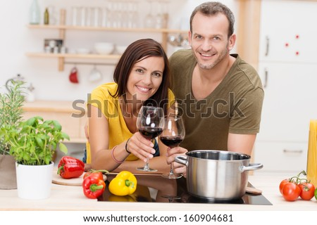 Cheerful young couple cooking a meal leaning side by side on the kitchen counter surrounded by fresh ingredients and each holding a glass of red wine - stock photo