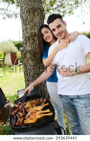 cheerful young couple cooking barbecue outdoor in summer garden party - stock photo