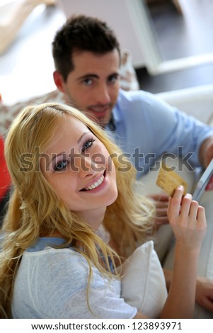 Cheerful young couple doing online shopping with tablet - stock photo