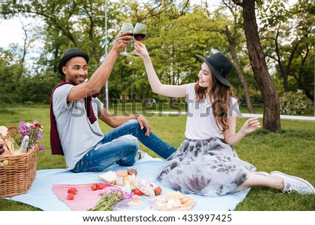 Cheerful young couple drinking wine on picnic in park - stock photo