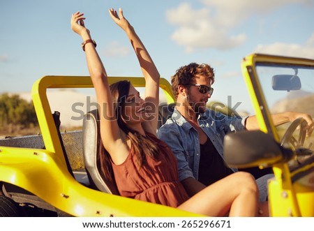 Cheerful young couple driving in a car. Enjoying road trip. Young man driving car with woman enjoying the ride with her hands raised. - stock photo