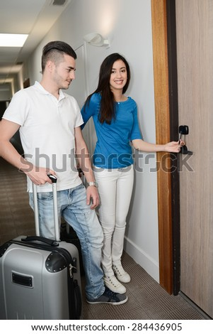cheerful young couple during vacation travel in a hotel holiday resort looking for their room in corridor