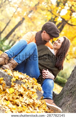 Cheerful young couple enjoy break on sunny autumn day, sitting under the tree in park and kissing